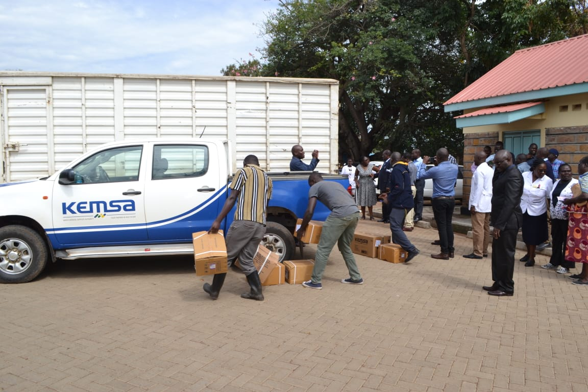 Offloaders carry the delivered medical commodities into the health facility as members of the public and the county Government watch.